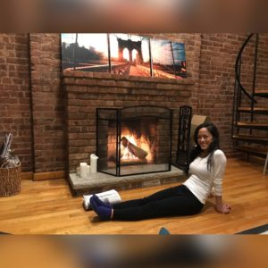 Tiana feeling very satisfied after starting her first fire in the fireplace, at our previous NYC home.