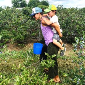 This is Elizabeth blueberry picking with her first nephew. They are close buddies