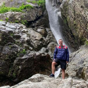 Parker standing in front of a waterfall while hiking in Willsboro, New York