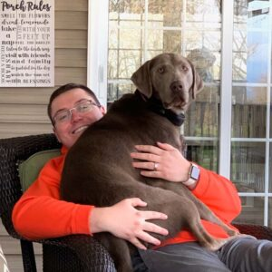 Parker relaxing on the porch at our house with our silver lab, Silo